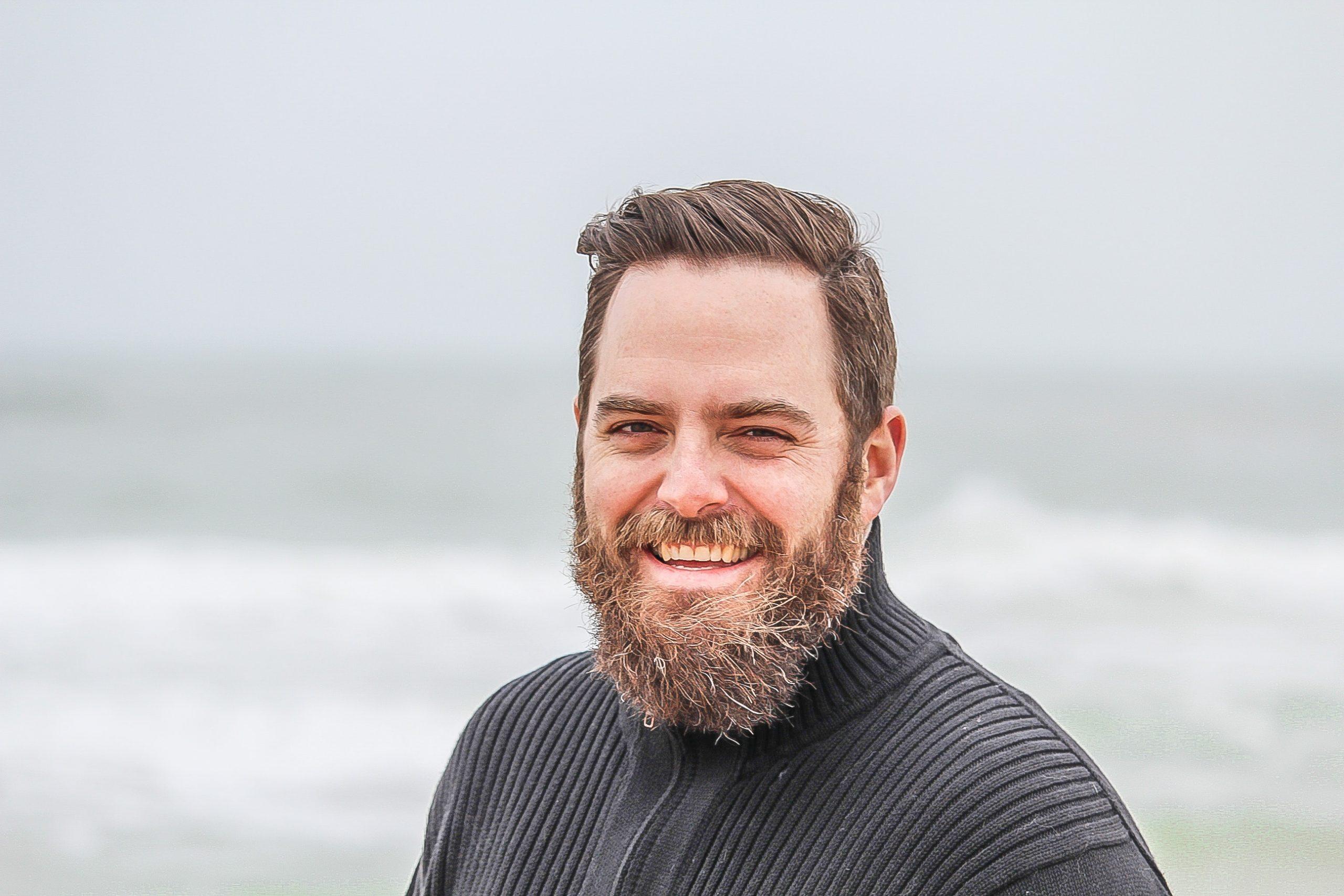 man-wearing-black-zip-up-jacket-near-beach-smiling-at-the-736716
